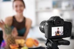 Weiblicher Blogger mit Früchten auf Kameraschirm Stockbilder