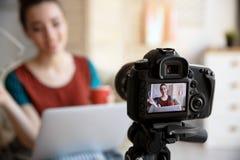 Weiblicher Blogger mit Laptop auf Kameraschirm Stockfotografie