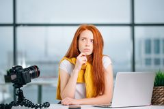 Weiblicher Blogger mit Laptop denkend an ein neues Thema für Videoblog Lizenzfreies Stockfoto