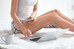 Weiblicher Blogger mit Laptop und Smartphone Lizenzfreie Stockfotos