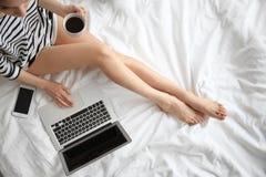 Weiblicher Blogger mit Laptop und Tasse Kaffee auf Bett Lizenzfreie Stockfotos