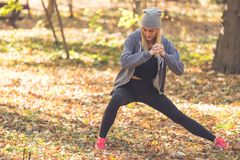 Weiblicher blonder Athlet, der Beine vor runn aufwärmt und ausdehnt Stockfoto
