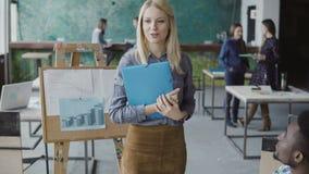 Weiblicher blonder Manager kommt zum jungen Geschäftsteam Gemischtrassige Gruppe von Personenen-Sitzung im modischen Hippie-Büro Lizenzfreie Stockbilder