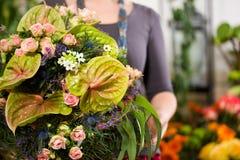 Weiblicher Blumenhändler im Blumensystem Stockbilder