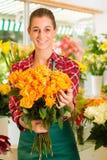 Weiblicher Blumenhändler im Blumensystem Lizenzfreie Stockfotos