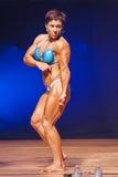 Weiblicher Bodybuilder biegt ihre Muskeln, die herein ihr Konstitution darstellen Stockfotografie