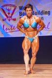 Weiblicher Bodybuilder biegt ihre Muskeln, um ihr Konstitution zu zeigen Stockbild