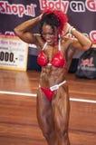 Weiblicher Bodybuilder in den abdominals und Schenkel werfen und roter Bikini auf Stockfotos