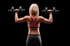 Weiblicher Bodybuilder, der mit Gewichten trainiert Lizenzfreie Stockfotos