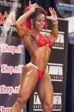 Weiblicher Bodybuilder im vorderen doppelten Bizeps werfen und roter Bikini auf Stockfotografie