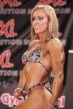 Weiblicher bodyfitness Kandidat zeigt Fronthaltung het gut auf Stadium Stockfoto