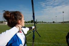 Weiblicher Bogenschütze, der mit ihrem Bogen zielt. Stockbilder