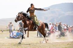 Weiblicher Bogenschütze, der zu Pferd einen Pfeil schießt lizenzfreie stockfotografie