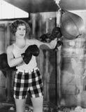 Weiblicher Boxer, der Sandsack verwendet (alle dargestellten Personen sind nicht längeres lebendes und kein Zustand existiert Lie Lizenzfreie Stockfotos