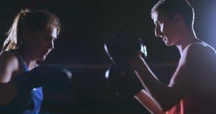 Weiblicher Boxer lochende Handschuhe eines Fokus mit Boxhandschuhen in einer rauchigen Turnhalle stock video