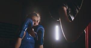 Weiblicher Boxer lochende Handschuhe eines Fokus mit Boxhandschuhen in einer rauchigen Turnhalle stock video footage