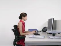 Weiblicher Büroangestellter, der Computer am Schreibtisch verwendet Stockbild