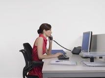 Weiblicher Büroangestellter, der Computer und Telefon am Schreibtisch verwendet Stockfotografie