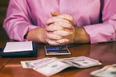 Weiblicher Buchhalter, der Geld mit Taschenrechner zählt Stockbilder