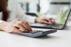 weiblicher Buchhalter, der Taschenrechner verwendet und auf Laptop schreibt stockfotografie