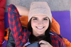 Weiblicher Camper, der im Schlafsack auf Matte liegt lizenzfreie stockfotos