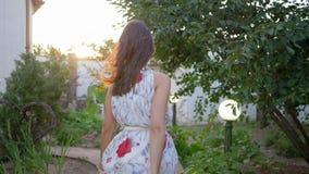 Weiblicher Charme, süßes Mädchen im Fliegenkleid geht und schaut herum im Hof unter Bäumen stock video
