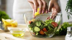 Weiblicher Chef übergibt das Zusammendrücken des frischen Zitronensaftes in Schüssel mit Salat, Vitamine lizenzfreies stockfoto