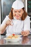 Weiblicher Chef-Adding Spices To-Teller Stockbild