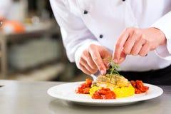 Weiblicher Chef beim Gaststätteküchekochen stockbild