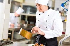 Weiblicher Chef beim Restaurantküchenkochen Stockfoto