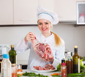 Weiblicher Chef, der mit Ziegenfleisch in der Küche arbeitet Lizenzfreie Stockfotografie