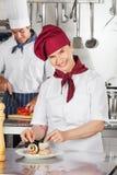 Weiblicher Chef Garnishing Salmon Roll Stockfotografie