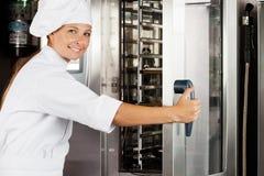 Weiblicher Chef Opening Oven Door Stockfotos