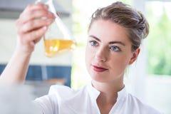 Weiblicher Chemiker, der Flasche hält Stockbilder
