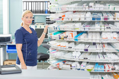 Weiblicher Chemiker Standing By Shelves in der Apotheke stockfotografie