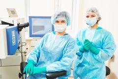 Weiblicher Chirurg mit behilflichem Raum in Kraft Lizenzfreie Stockbilder
