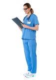 Weiblicher Chirurg mit dem Stethoskop, Report lesend Stockfotos