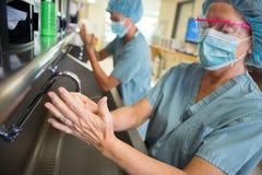 Weiblicher Chirurg Scrubbing Hands und Arme lizenzfreie stockbilder