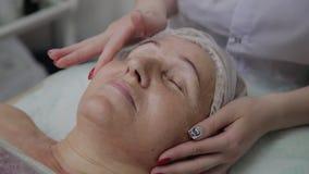 Weiblicher Cosmetologist, der Gesichtsmassage ältere Frau in der cosmetological Klinik antut stock footage