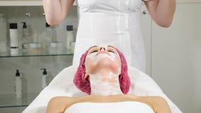 Weiblicher Cosmetologist wischt Gesicht nach einer Sch?nheitsmaske weg vom weiblichen Kunden ab Abschluss oben Frau, die Hautbeha stock footage