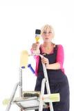 Weiblicher Dekorateur auf einer Strichleiter lizenzfreie stockfotografie