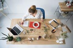 Weiblicher Dekorateur mit Kranz, trockenen Blumen und Laptop am Arbeitsplatz lizenzfreie stockbilder