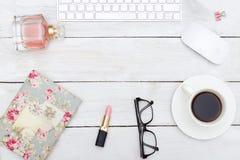 Weiblicher Desktop mit Zubehör auf weißem hölzernem Hintergrund Stockfotos