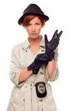 Weiblicher Detektiv mit dem Abzeichen, das auf Handschuhe sich setzt Stockbilder