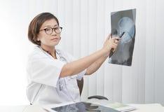 Weiblicher Doktor, der auf Hauptschädel-Röntgenfilm überwacht Stockfotos
