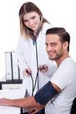 Weiblicher Doktor, der Blutdruck überprüft Stockbilder