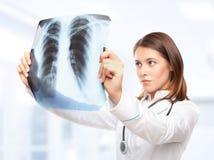 Weiblicher Doktor, der den Röntgenstrahl betrachtet Stockfoto
