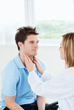 Weiblicher Doktor, der die Kehle eines Patienten berührt Lizenzfreies Stockfoto