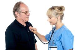 Weiblicher Doktor, der einen älteren Mann überprüft Lizenzfreies Stockbild