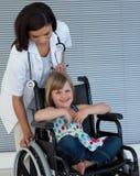 Weiblicher Doktor, der einen Rollstuhl drückt stockbild